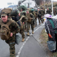 A woman bows to U.S. Marines who have arrived on Miyagi Prefecture's Oshima Island in April 2011 to assist in clearing the debris left behind by the March 11 disasters. | III MARINE EXPEDITIONARY FORCE / MARINE CORPS INSTALLATIONS PACIFIC