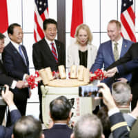 Prime Minister Shinzo Abe and two relatives of U.S. President Dwight D. Eisenhower are joined by other Japanese and U.S. officials as they celebrate the 60th anniversary of the signing of the Japan-U.S. security treaty in Tokyo on Jan. 19. | REUTERS