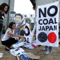 People prepare for a rally in Kobe last June 27 to protest Japan's support for new coal-fired power generation projects.  | BLOOMBERG