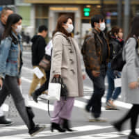 Pedestrians cross a street in Tokyo's Ginza district on Saturday. Japan's economy likely suffered its biggest contraction since 2014 at the end of last year leaving it in a vulnerable state as fallout from China's viral outbreak threatens to turn a one-quarter slump into a recession. | BLOOMBERG