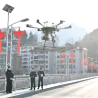 Police officers operate a drone to spread information about the prevention and control of the new coronavirus, in Xiangyang, Hubei province on Feb. 4. | REUTERS