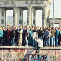 People stand on the Berlin Wall near the Brandenburg Gate in Berlin on Nov. 9, 1989. East and West Germany united on Oct. 3, 1990, after more than 45 years of division. | SUE REAM