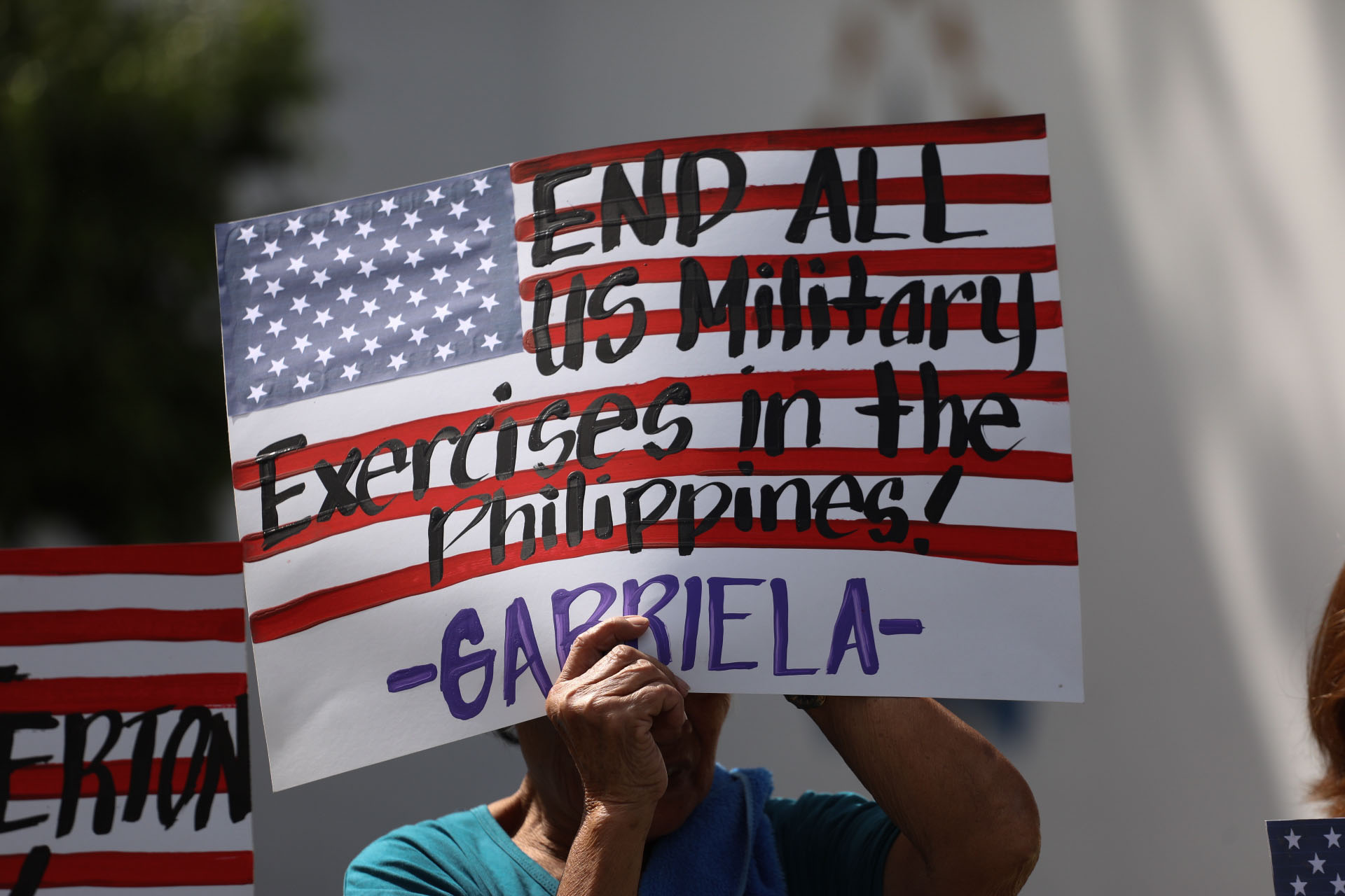 Demonstrating in front of the Department of National Defense in Manila on Friday, members of the activist group Gabriela Alliance for Women call for the termination of U.S.-Philippines military exercises for 2020. | AFP-JIJI