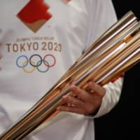 Greek singer Sakis Rouvas wears the uniform of the the 2020 Tokyo Olympic Games torch relay runners as he holds the torch during a presentation in Athens on Monday. | AP