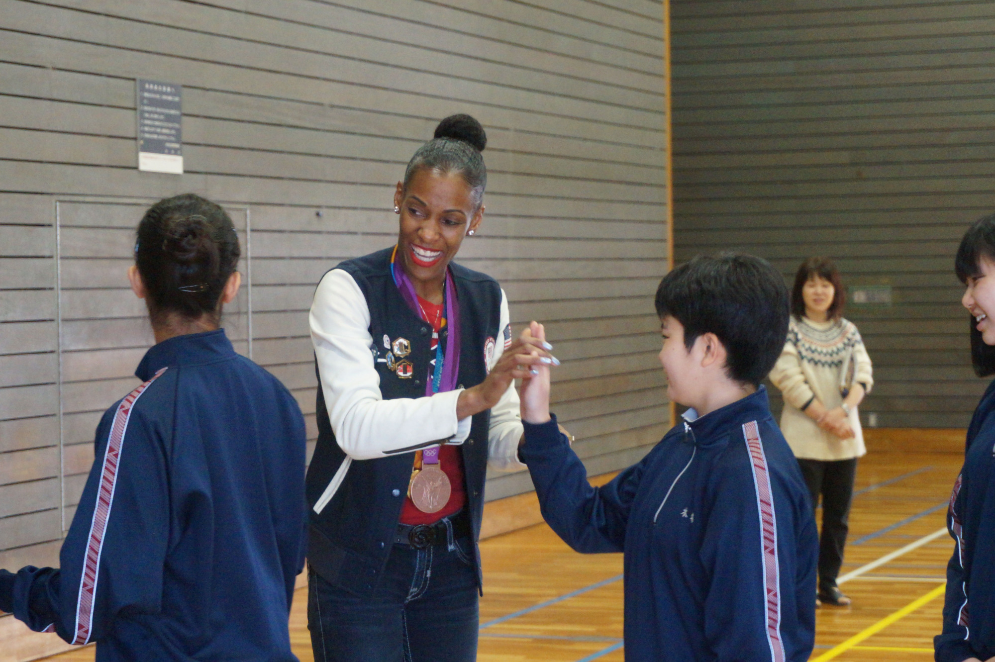 Two-time Olympic gold medalist DeeDee Trotter (center) interacts with students at Funabashi Kibou Junior High School in Tokyo's Setagaya Ward on Tuesday. | JASON COSKREY