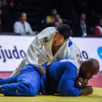 Kokoro Kageura (top) competes against France's Teddy Riner during their match at the Paris Grand Slam on Sunday in Paris. | AFP-JIJI