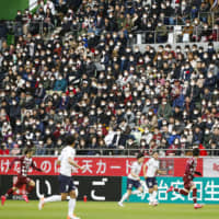 J. League fans wear masks to protect themselves as a precautionary measure during the coronavirus outbreak on Sunday during a Vissel Kobe home match at Noevir Stadium. | KYODO