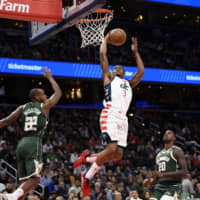 The Wizards' Bradley Beal goes to the basket against the Bucks' Khris Middleton and Marvin Williams in the second half on Monday in Washington. | AP