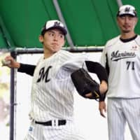 Marines rookie Roki Sasaki delivers as pitching coach Masato Yoshii watches during a bullpen session on Thursday in Ishigaki, Okinawa Prefecture. | KYODO