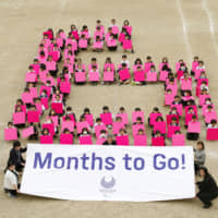 Third-grade students from Ariake Nishi Gakuen in Tokyo line up to create a giant No. 6 to mark the six-month countdown to the 2020 Paralympics on Tuesday. | KYODO