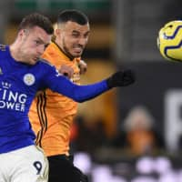 Leicester City's Jamie Vardy (left) and Wolverhampton's Romain Saiss vie for the ball in a Premier League match on Friday night in Wolverhampton, England. | AFP-JIJI