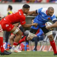 Toshiba's Michael Leitch tries to evade a tackle during a Top League game against Kobelco on Sunday.  The upcoming two rounds of the league have been postponed due to the ongoing coronavirus outbreak. | KYODO