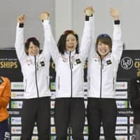 Japan team pursuit speedskaters (from left) Nana Takagi, Miho Takagi and Ayano Sato celebrate on the podium after breaking their own world record in the event on Friday at the ISU World Single Distances Speed Skating Championships in Salt Lake City. | KYODO