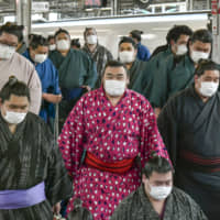 Rikishi wearing protective face masks arrive at Shin-Osaka Station ahead of next month's Spring Grand Sumo Tournament in Osaka. | KYODO