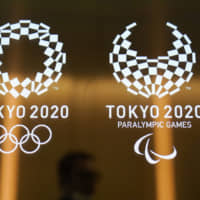 A man walks past the logos for the 2020 Tokyo Olympics and Paralympics on June 11, 2019. | AP