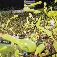 Fans release balloons into the air during a Hanshin Tigers game in August 2019 at Koshien Stadium. | KYODO