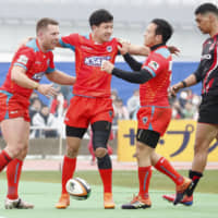 Kubota Spears players celebrate a try by Bernard Foley (left) during a Top League match against Hino Red Dolphins on Sunday at Tokyo's Yumenoshima Stadium. | KYODO