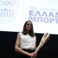 Greek actress Xanthi Georgiou holds the torch for the 2020 Tokyo Olympics during a presentation in Athens on Monday. | AP