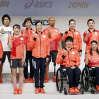 Japan Olympians and Paralympians pose in national team casual attire at a Friday news conference. | KYODO
