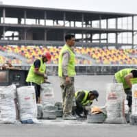 Workers set up a curb at the under-construction Formula One Vietnam Grand Prix race track in Hanoi on Friday. | AFP-JIJI