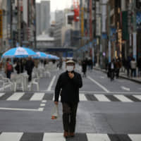A man wearing a protective face mask walks on a street in Tokyo's Ginza district on Saturday.  | REUTERS