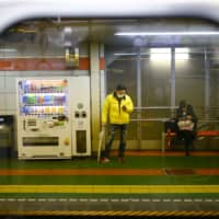 A man, wearing a protective face mask, following an outbreak of the COVID-19 virus, looks on his mobile phone inside a subway station in Tokyo. A 44-year-old man in Shimane Prefecture has been arrested after he pretended to have contracted the virus and threatened to spread it at a local train station, NHK reported Saturday. | REUTERS
