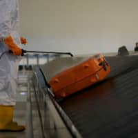 A worker sprays disinfectant on a travel bag on a conveyor at the international terminal of Soekarno-Hatta Airport near Jakarta.  | REUTERS