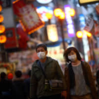 A couple, wearing protective masks walk on an almost empty street in the Dotonbori amusement district of Osaka on March 14. | REUTERS