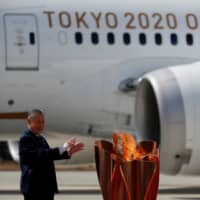 Three-time Olympic gold medalists Tadahiro Nomura and Saori Yoshida pose after lighting the Olympic Flame at the Olympic cauldron while watched by Tokyo 2020 Olympics President Yoshiro Mori (left) during a ceremony at Japan Air Self-Defense Force Matsushima Base in Higashi-Matsushima, Miyagi Prefecture on March 20. | AFP-JIJI