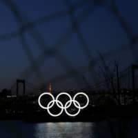 The giant Olympic rings are seen in the dusk through a steel fence at the waterfront area at Odaiba Marine Park after postponing Games due to the outbreak of coronavirus disease in Tokyo on March 25. | REUTERS