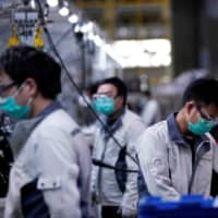Employees wearing masks work on a car seat assembly line at the Yanfeng Adient factory in Shanghai on Feb. 24. | REUTERS