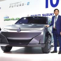 Kenichi Ayukawa, managing director and CEO of Maruti Suzuki India Ltd., a subsidiary of Suzuki Motor Corp., shows off a prototype electric vehicle at the Auto Expo in Greater Noida, near New Delhi, on Feb. 5. | KYODO