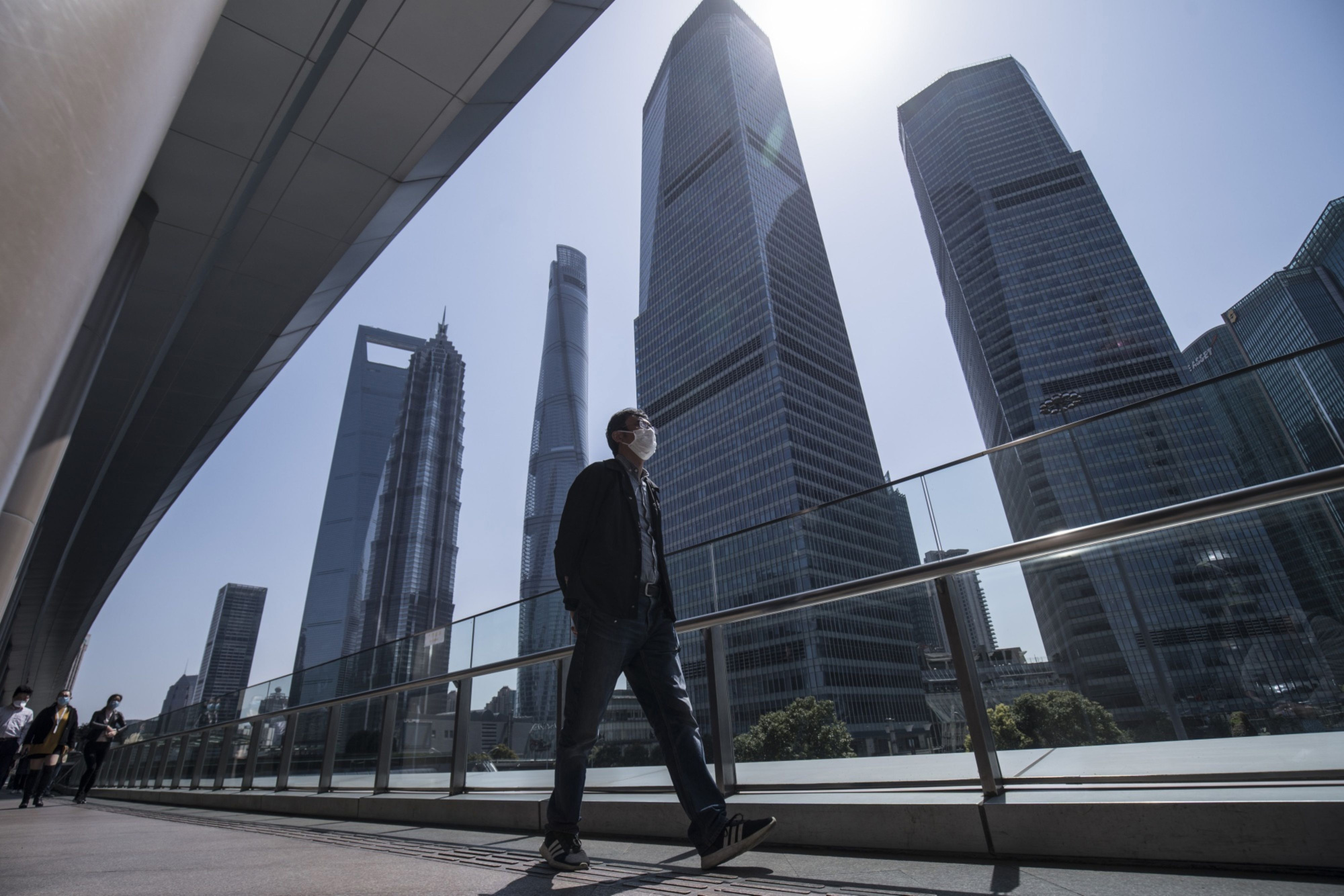 A pedestrian with a mask walks through the Lujiazui Financial District in Shanghai on Friday. | BLOOMBERG