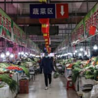 A customer looks at vegetables at a market in Shenyang in northeastern China on Monday. A survey shows that Chinese consumer sentiment has remained relatively strong compared with that in many countries hit by the coronavirus outbreak, including Japan. | AFP-JIJI