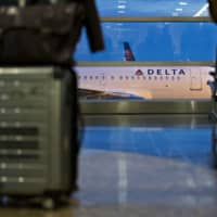 A Delta Air Lines Inc. plane is parked outside a terminal near at Ronald Reagan National Airport in Washington in November 2017. | BLOOMBERG