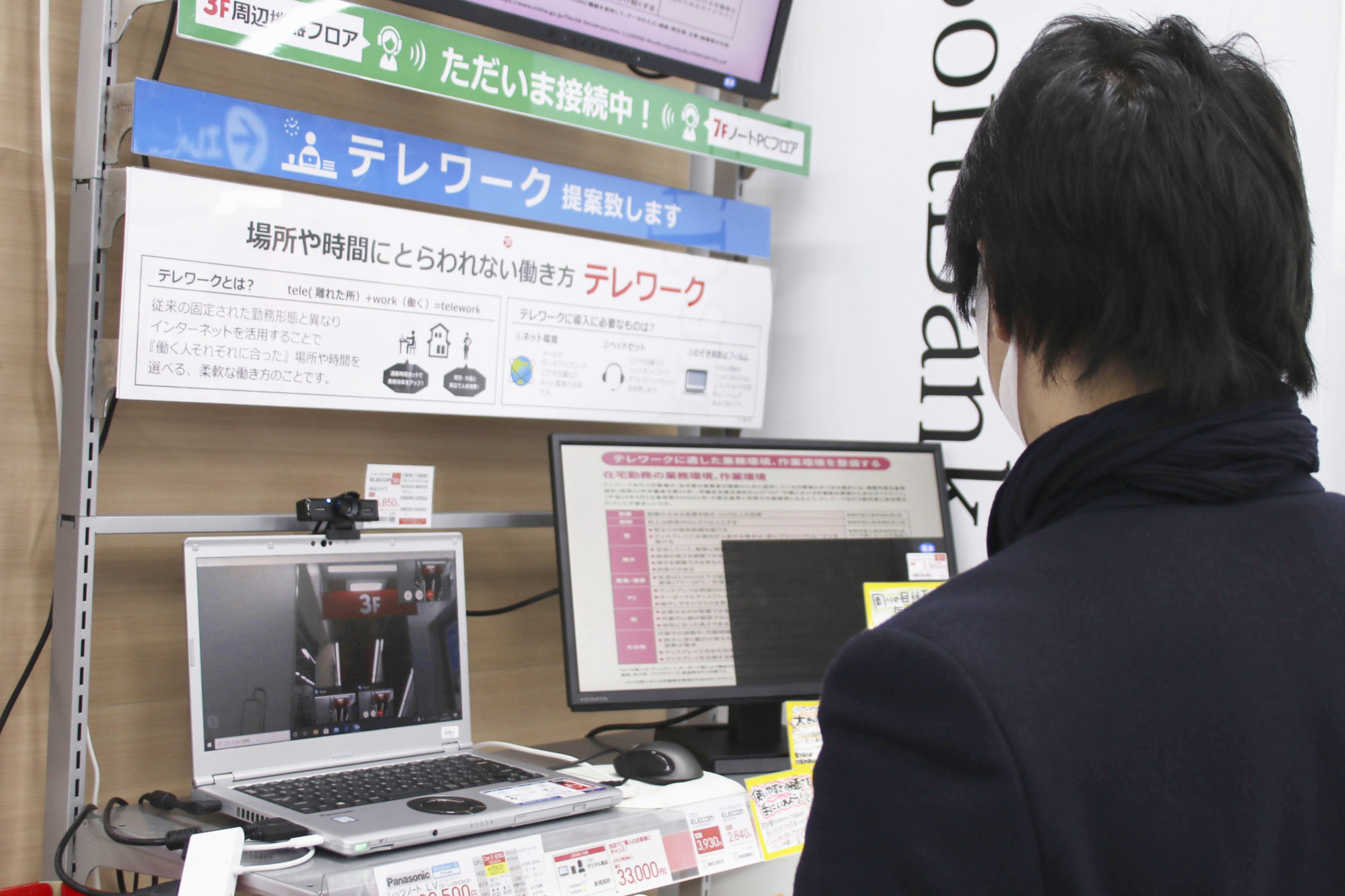 A shopper checks out devices that streamline telecommuting Thursday at BicCamera Inc.'s flagship outlet in Tokyo's Ikebukuro district. | KYODO