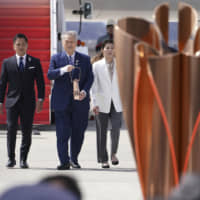Tokyo 2020 Olympics chief Yoshiro Mori (third from left), followed by three-time Olympic gold medalists Tadahiro Nomura and Saori Yoshida, carries the Olympic flame during the arrival ceremony at Japan Air Self-Defense Force Matsushima Base in Higashimatsushima in Miyagi Prefecture on Friday. | AP