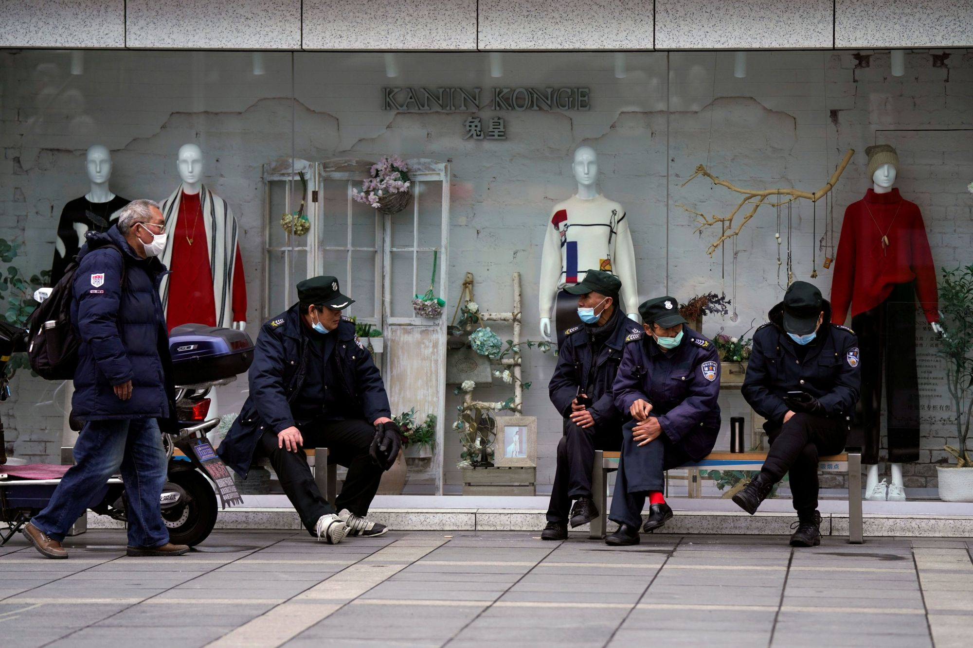 Security guards wear protective face masks outside a shopping mall in Shanghai on Sunday. | REUTERS
