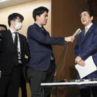 Prime Minister Shinzo Abe speaks to reporters at his office Monday night after talking with Group of Seven leaders in a teleconference. | KYODO