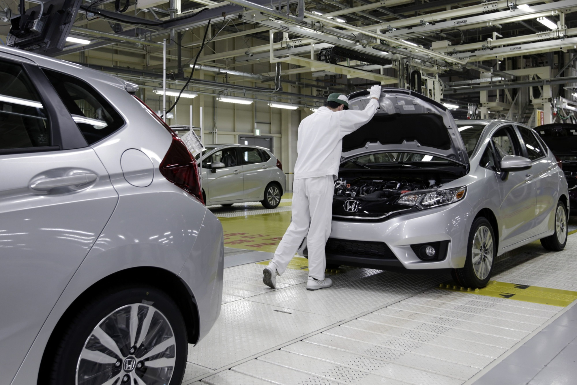 A Honda employee gives a Fit the final inspection at the automaker's Yorii plant in Saitama Prefecture.   BLOOMBERG