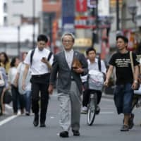 Retiree Sadao Sekine walks down a street in the city of Saitama. The government  Tuesday decided to reform the pension system to expand the range of part-time workers who can join the kōsei nenkin public pension program for corporate employees. | BLOOMBERG