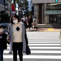 People wear protective masks in Tokyo on Tuesday. | REUTERS