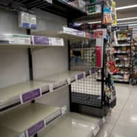 A masked employee works near shelves emptied by panic-buying of toilet paper and tissues at a supermarket in Tokyo on Wednesday.   REUTERS