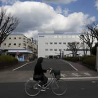 A cyclist rides past the Toto Ltd. factory in Kitakyushu in January 2017. | BLOOMBERG