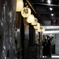 Restaurant employees with masks wait for customers at the Tsukiji Outer Market in Tokyo on Thursday. | BLOOMBERG