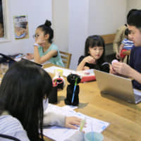Parents work alongside their children at a cafe in Tokyo during an experimental telecommuting event last year.   KYODO