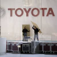 Workers dismantle a Toyota Motor Corp. pavilion at the canceled Geneva International Motor Show. Toyota said its idled manufacturing facilities in the U.S. will make face shields and masks. | BLOOMBERG
