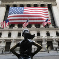 The Fearless Girl statue stands in front of the New York Stock Exchange on Monday. The U.S. stock market plunged to its worst day in more than three decades as voices from Wall Street to the White House said the coronavirus may be dragging the economy into a recession. | AP
