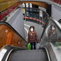 A woman leaves a supermarket at a nearly empty mall in Beijing on Thursday. | AFP-JIJI