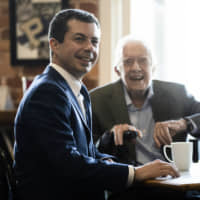 Democratic presidential candidate and former South Bend, Indiana, Mayor Pete Buttigieg meets with former President Jimmy Carter at the Buffalo Cafe in Plains, Georgia, on Sunday. | AP
